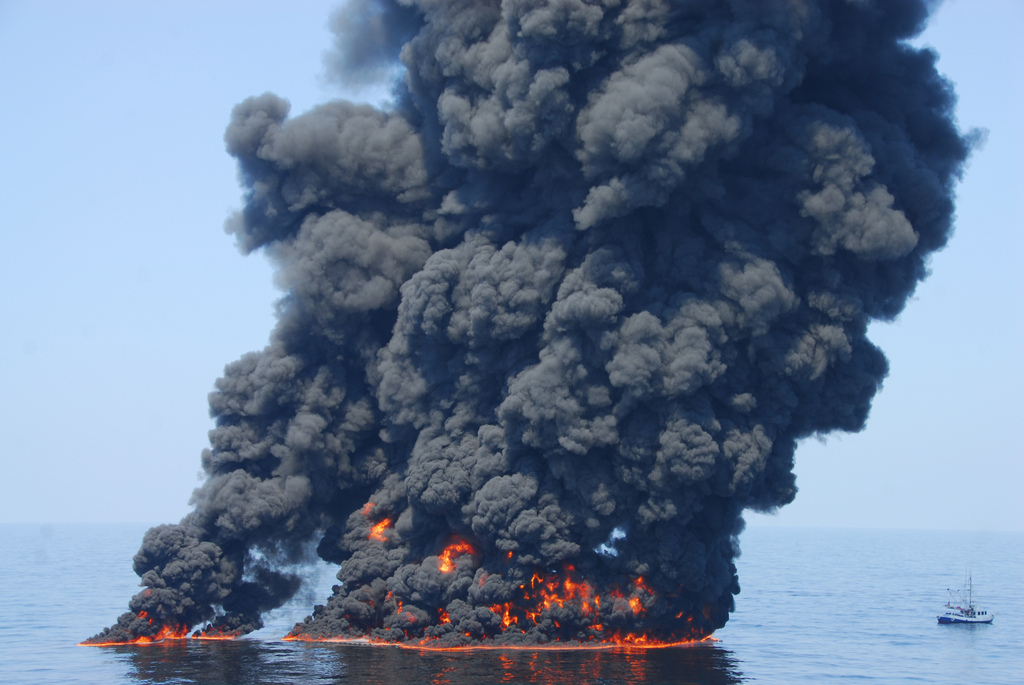 A enormous smoke plume on the ocean next to a boat which looks small in comparison.