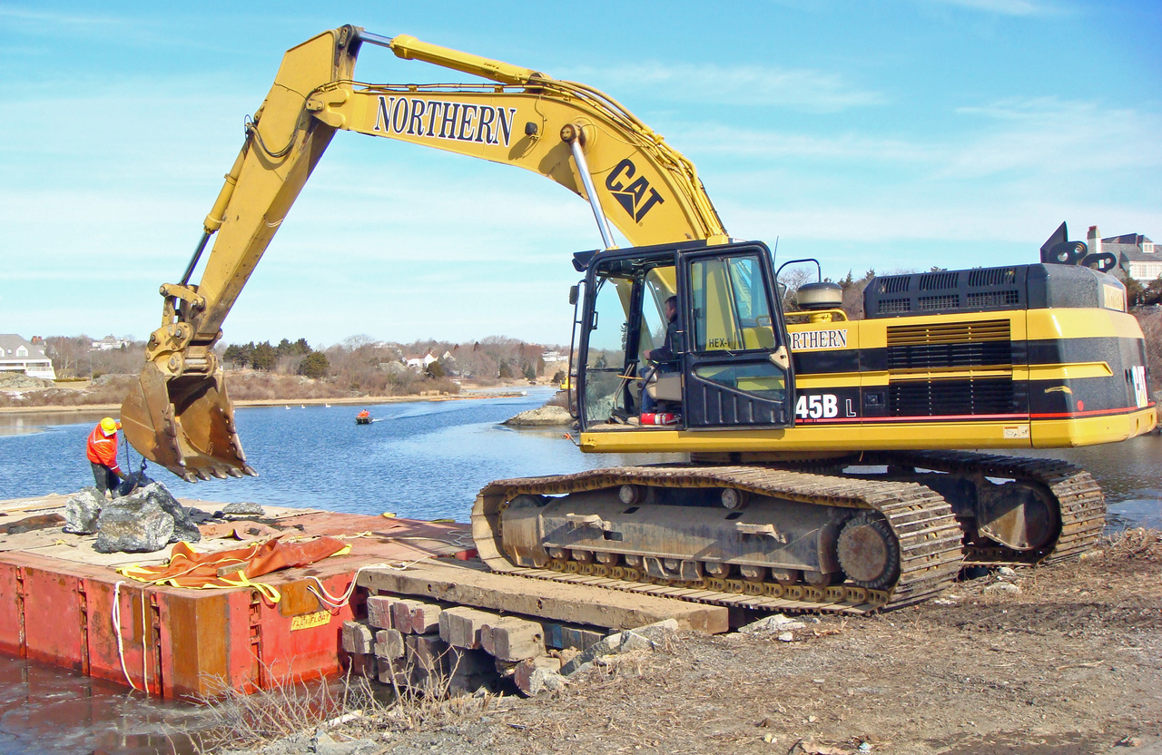 A earth mover at the edge of a waterway.