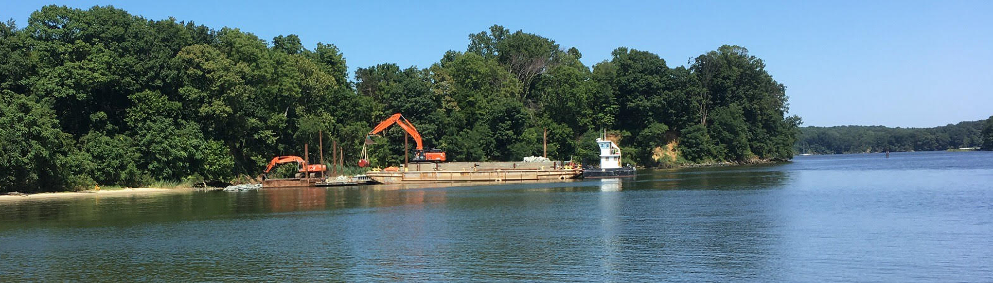 Two excavator machines work on building a shoreline project. A barge holding materials is in the water offshore.