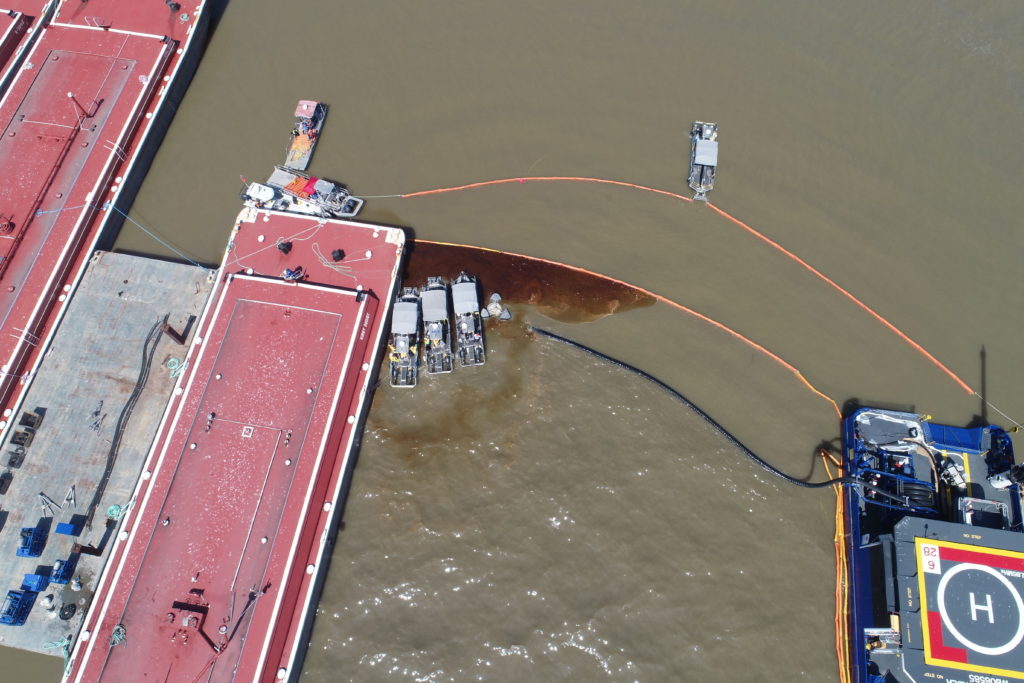 Aerial view of skimmers containing oil on brown water.