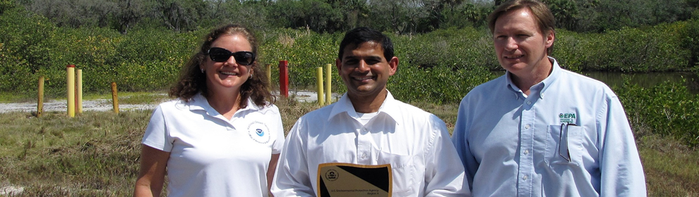 Dr. Michel Gielazyn (left) with Raghu Chatrathi (middle) Director of Environmental Remediation, Engineering and Advance Technologies (CSX/ALI), and Michael Taylor, EPA Region 4 Remedial Project Manager (right). Restored marsh is in the background.