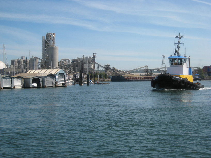 A boat navigates the Lower Duwamish River with industrial development on both sides of the river's banks.