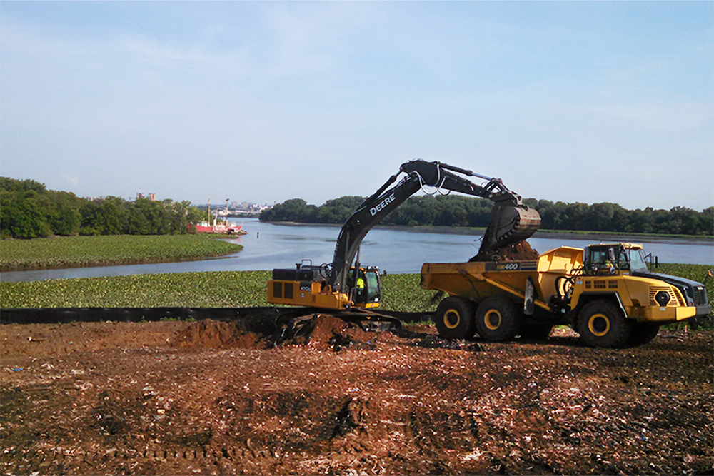 Heavy machinery excavates near where the Delaware River converges with the Cooper River