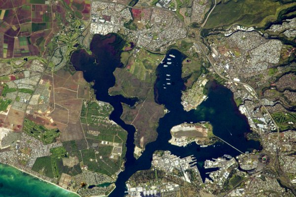 A satellite image of a blue harbor surrounded by roads and human development (NASA).