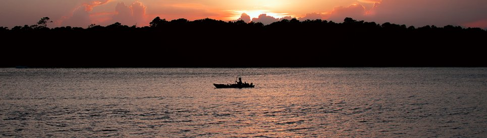 An angler on a boat on the Cape Fear River at sunset.