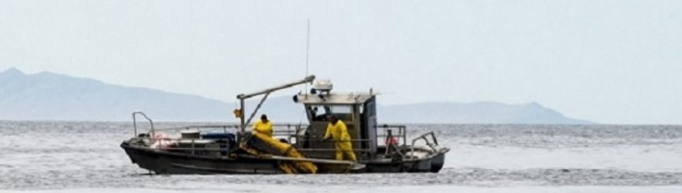 Crews recover boom from Refugio Beach Oil Spill.