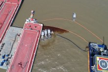Overhead view of skimmers containing oil on brown water.