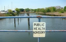 A warning sign cautions people can be exposed to site-related contaminants at Tidal Ferry Creek.