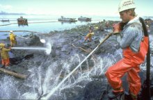 Cleanup workers spray oil-covered rocks on Prince William Sound with high-pressure hoses. (Exxon Valdez Oil Spill Trustee Council)