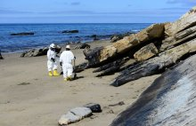 Two cleanup workers in white protective gear and yellow boots stand next to oiled rocks and ocean in background.