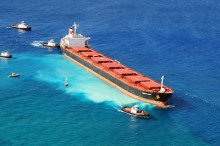 The 734-foot bulk carrier M/V VogeTrader after it ran aground near Oahu, on February 5, 2010. The milky color in the water beneath the ship is the pulverized coral. (USCG)