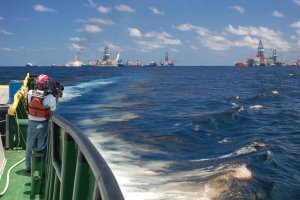 National Geographic videographer Bob Perrin films an oil slick at the Deepwater Horizon site. Image credit: NOAA