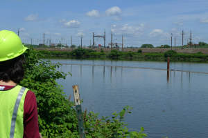 Woman in construction hat in foreground with river, bird, and industrial buildings in the background.