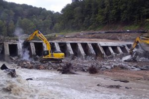 Two excavators hammer away at the Bloede Dam on a river shortly after its breach. Credit: Maryland Department of Natural Resources.