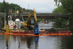 A barge with a earth mover scoops sediment from a river with a bridge in background.