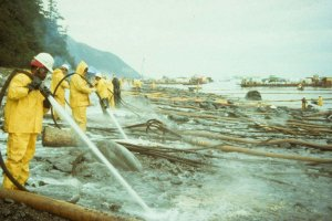 A line of clean-up workers hose off oil from a rocky shore using hot water following the Exxon Valdez oil spill. Photograph credit: Exxon Valdez Oil Spill Trustee Council