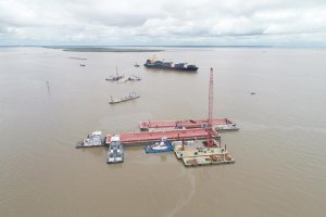 A overflight photo of vessels surrounding damaged barges in brown water.