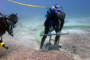 Divers remove the thick layer of coral rubble from the seafloor using a vacuum hose attached to a boat.