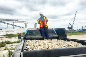 A woman in a mask and gloves gives a thumbs up while standing on a truck pickup-bed full of white oyster shells.